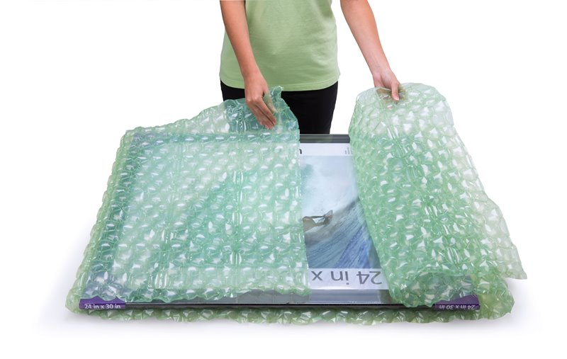 Person using AirPouch High Loft FastWrap to protect a large picture frame